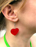 Lady wearing heart earring. Closeup of a woman wearing a red heart dangling earing royalty free stock images