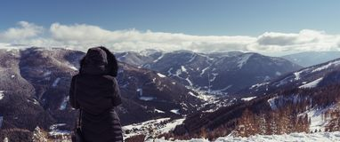 A lady wearing a hooded jacket looks down from the mountain into the wide open valley stock photography