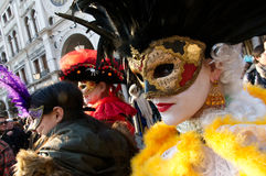 Lady wearing a mask. A beautiful lady is wearing a mask surrounded by tourists and other masks during the carnival in Venice Italy Royalty Free Stock Photos
