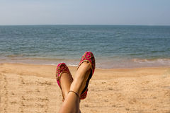 A lady wearing a pair of pink traditional Indian women`s shoes jutis at the Anjuna beach in Goa, India Royalty Free Stock Images