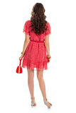 Lady wearing short sleeve dress. Red dress and thin belt. Stylish purse and wrist accessories. Back view of female model Stock Photos