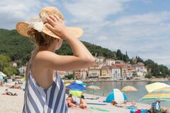 Free Lady Wearing Striped Summer Dress And Straw Hat Relaxing On Vaction Enjoying View Over Beach At Moscenicka Draga, Istria Royalty Free Stock Photography - 191360727