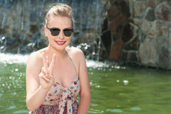 Lady wearing sun glasses and showing peace gesture Royalty Free Stock Photos