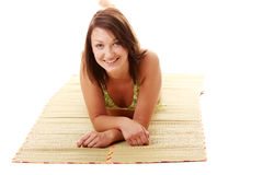Lady wearing swimsuit on bamboo mat Stock Photo