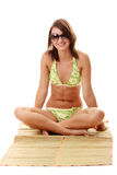 Lady wearing swimsuit on bamboo mat Royalty Free Stock Photography