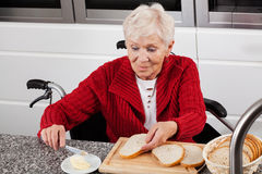 Lady on wheelchair making breakfast Royalty Free Stock Photography