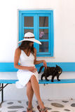 Lady  in white and a cat in front of a classic, Greek, blue window Royalty Free Stock Photos