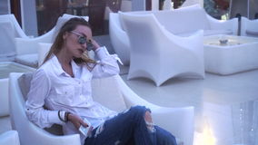 Lady in white clothes sits outdoors in chair stock footage
