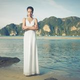 Lady in white dress on a seashore. Portrait of beautiful lady in white dress on seashore Stock Photo