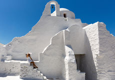 Lady in white dress sits at the stairs of the Paraportiani Church of Mykonos, Greece Royalty Free Stock Image