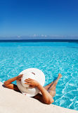 Lady with white hat relaxes in swimming pool Stock Photography