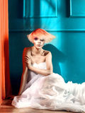 Lady with white-red hair. Beautiful young lady with a white-red hair in blue interior Royalty Free Stock Image