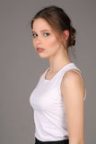 Lady in white singlet standing profile. Close up. Gray background Stock Image