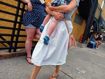 Lady holding a baby walks along the sidewalk as another woman leans against a railing. stock photography