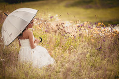 Lady in white with umbrella on the meadow Royalty Free Stock Photos