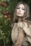 Lady of the wild meadows. Young beauty lady stays under an apple tree Stock Photography