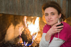 Lady, wine, fireplace Royalty Free Stock Image