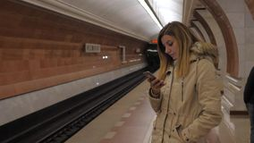 Lady Winter Jacket Waiting Train On Station Platform, Metro Uses Smartphone. A young pretty brunette lady in a warm winter jacket stands on a subway station stock video footage