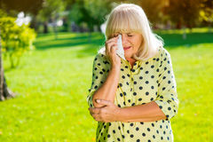 Lady wiping eye with handkerchief. Stock Image