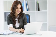 Lady at work. Charming young woman in formalwear computing in office Royalty Free Stock Image
