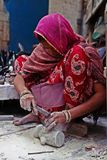 A lady worker stone carving on a street of India Stock Images