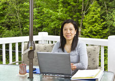 Lady working at home on outdoor patio Royalty Free Stock Photos