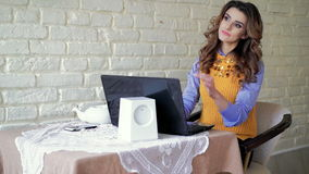 Lady working with laptop, touching hair and looking in cafe stock video footage