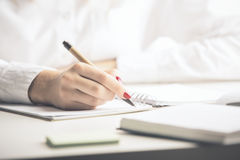 Lady writing in notepad Royalty Free Stock Photos