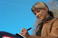 Lady Writing Outdoors Stock Images
