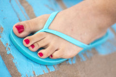 Lady& x27;s feet in sandals on beach Stock Photography