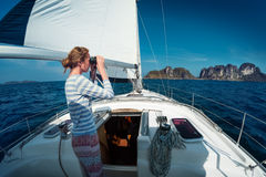 Lady on the yacht. Lady sailor standing on the yacht and watching to the binoculars at sunny day stock image