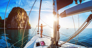 Lady on the yacht. Young lady standing on the bow of yacht and doing exercise at sunrise stock photo