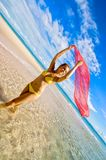 Lady in yellow bikini. Women in yellow bikini with red scarf down at the beach,  It is a warm summers day the sky is royal blue in colour, the ocean crystal Royalty Free Stock Image