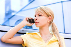 Lady in yellow talk by phone. Near blue wall Stock Images