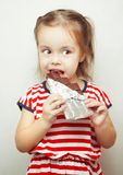 Lady of young age eating chocolate wrapped in tinfoil. Lady of young age, dressed in clothes with pattern of red and white stripes, in process of eating Royalty Free Stock Images