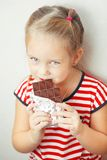 Lady of young age eating chocolate wrapped in tinfoil. Lady of young age, dressed in clothes with pattern of red and white stripes, in process of eating Royalty Free Stock Photo