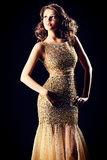 Lady young. Fashion shot of a stunning woman in luxurious golden dress. Over black background Stock Image
