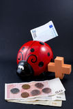 Ladybug money box and coins on black background Royalty Free Stock Image