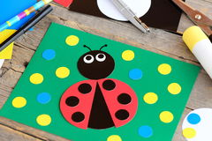 Ladybug paper collage. Ladybug card, stationery on a vintage wooden table. Children paper craft activity at home, in kindergarten Stock Photo