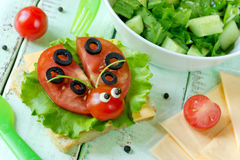 Ladybug sandwich. With cheese, green salad and tomato royalty free stock image