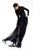 Beröm. Den flott kvinnadansen i lång svart klänning och maskerar. Tappning utformar royaltyfri foto