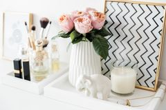 Ladys dressing table decoration with flowers, beautiful details,. Luxurious perfumes and makeup tools. White expensive interior decor closeup stock photo
