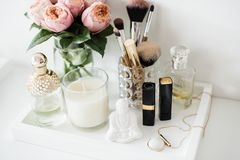 Ladys dressing table decoration with flowers, beautiful details,. Luxurious perfumes and makeup tools. White expensive interior decor closeup royalty free stock photo