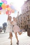 Ladys hermosos de Teo en el equipo retro que sostiene un manojo de globos Fotografía de archivo libre de regalías