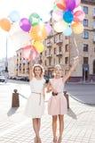 Ladys hermosos de Teo en el equipo retro que sostiene un manojo de globos Imagenes de archivo