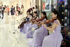 4 ladys spelar fiolen i en shoppinggalleria, magin av musik Arkivfoton