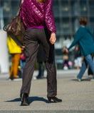 Laförsvar, Frankrike April 09, 2014: stående av affärskvinnan som går med påsen på en gata och höga häl Hon bär mycket en colorf Royaltyfri Bild