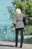 Laförsvar, Frankrike April 10, 2014: stående av en affärskvinna som går med påsen på en gata Hon ser mycket tillfällig, och det f Royaltyfri Bild