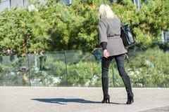 Laförsvar, Frankrike April 10, 2014: stående av en affärskvinna som går med påsen på en gata Hon ser mycket tillfällig, och det f arkivfoto