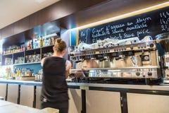 Laförsvar, Frankrike - Juli 17, 2016: oskarp kvinnlig bartender i stor traditionell fransk restaurang i laförsvarstaden, den stör fotografering för bildbyråer